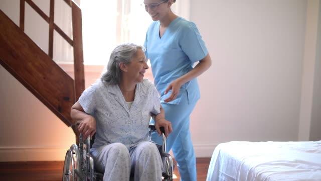 nurse helping senior woman with wheelchair in nursing home - retirement community stock videos & royalty-free footage