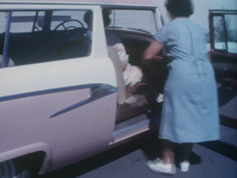 a nurse helps a new mother and her infant into a waiting car; a new mother holds her infant. - image stock videos & royalty-free footage