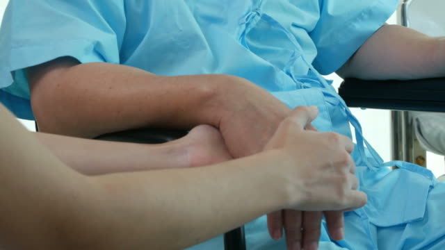 nurse hold one's hand and consoling to mature patient