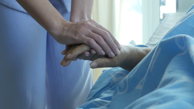 vídeos de stock e filmes b-roll de nurse hold one's hand and consoling to senior patient - fim