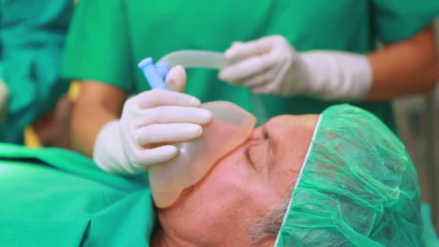Nurse holding an anesthesia mask next to surgeons
