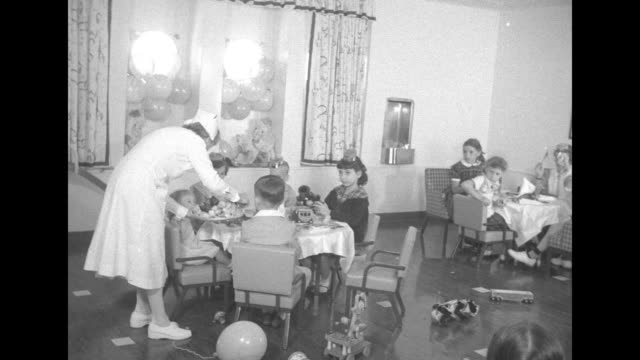 nurse in a white uniform attends to children seated at a round table; they wear party hats and two wave a noisemaker; small children on a small slide... - nursery bedroom stock videos & royalty-free footage