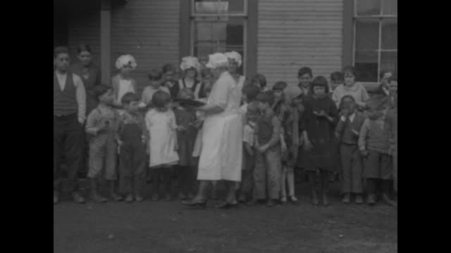 nurse in a white uniform moves along a diverse line of children handing out food / a little african-american boy sits with two white children on... - documentary footage stock videos & royalty-free footage