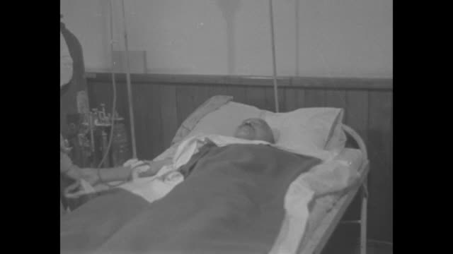 US nurse looks on as former Japanese Prime Minister Hideki Tojo lies with eyes closed in hospital bed after suicide attempt at conclusion of World...