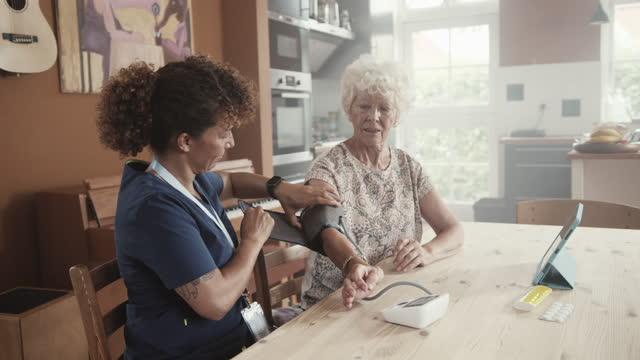 nurse measuring blood pressure of senior woman - ponytail stock videos & royalty-free footage