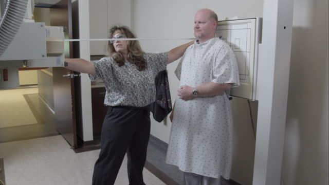 Nurse measuring distance from scanner to patient.