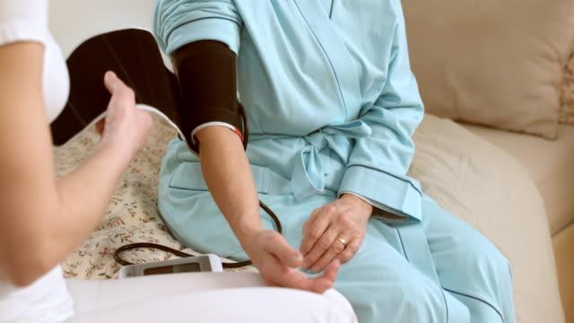 ds nurse measuring senior woman's blood pressure at her home - blood pressure gauge stock videos & royalty-free footage