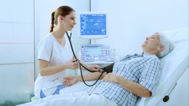 Nurse measuring senior womans blood pressure