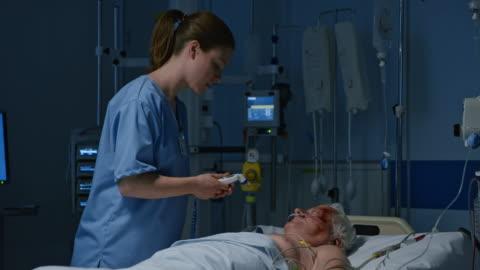 vídeos y material grabado en eventos de stock de ds personal de enfermería medir temperatura del paciente en la unidad de cuidados intensivos - plano de plataforma rodante