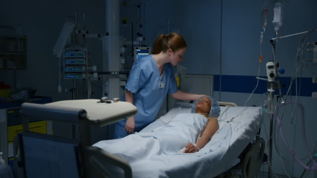 ds nurse observing a female patient lying in the intensive care unit - ward stock videos & royalty-free footage