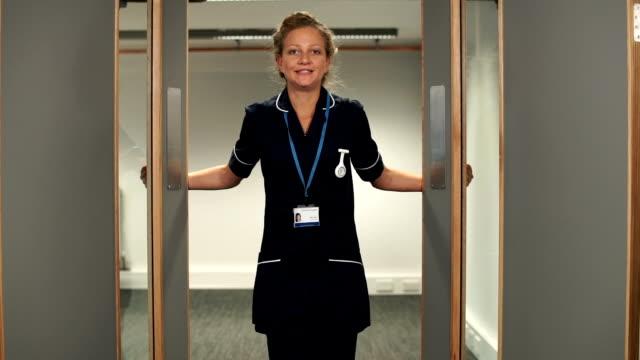 stockvideo's en b-roll-footage met nurse opens hospital doors takes a deep breath and walks straight to camera - nhs
