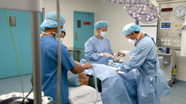 nurse passing medical tools to surgeon - operating room stock videos and b-roll footage