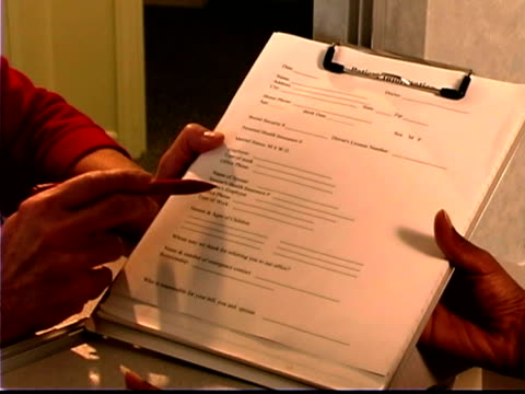 A nurse points areas out on a form that the patient must fill out.