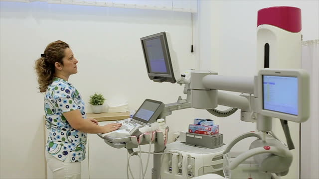 nurse preparing medical ultrasound scanner for doctor and patient - proiezione evento pubblicitario video stock e b–roll