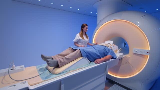 vídeos de stock, filmes e b-roll de enfermeira do ds preparando paciente antes de entrar no scanner de ressonância magnética - tomografia