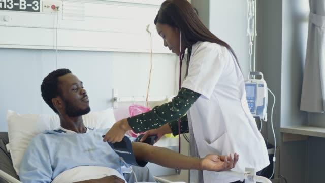 nurse preparing patient for blood pressure check at hospital ward - blood pressure gauge stock videos & royalty-free footage