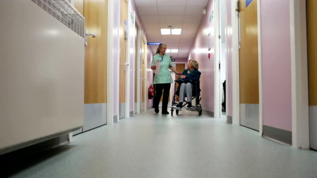 nurse pushes elderly woman down corridor in wheelchair - nhs stock videos & royalty-free footage