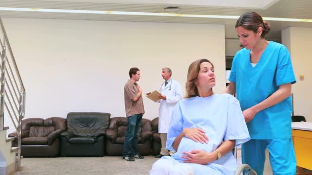 Nurse pushing a pregnant woman in a wheelchair