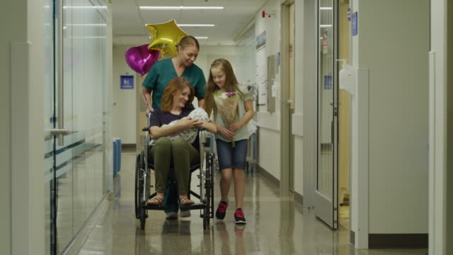 nurse pushing mother with newborn in wheelchair while daughter carries flowers / salt lake city, utah, united states - newborn stock videos & royalty-free footage