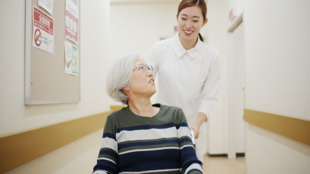 vídeos de stock e filmes b-roll de nurse pushing patient in wheelchair down hospital corridor - east asian ethnicity