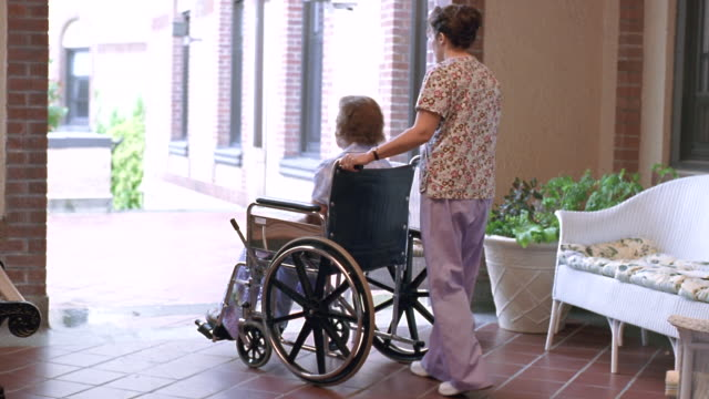 WS Nurse pushing senior woman in wheelchair / Washington State, USA