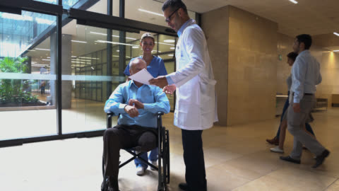 nurse pushing wheelchair with senior amputee patient while he greets doctor both looking at some test results very happy - building entrance stock videos & royalty-free footage