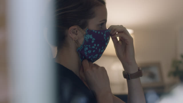 cu of nurse putting on protective face mask and cap. - ponytail stock videos & royalty-free footage