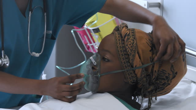 nurse putting oxygen mask over young woman's face - headdress stock videos & royalty-free footage