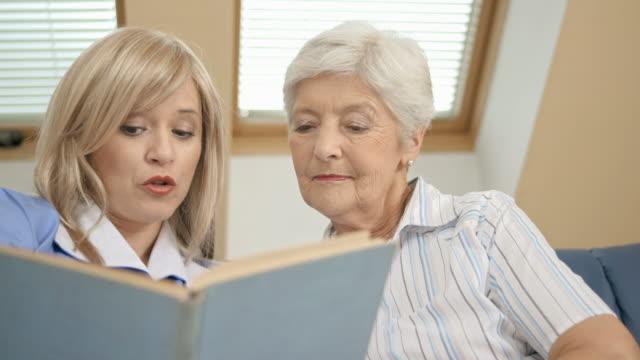 DOLLY HD: Enfermera leyendo un libro en un asilo de ancianos