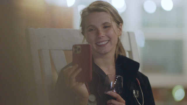 nurse relaxes after work with wine and video chatting with friends. - happy hour video stock e b–roll