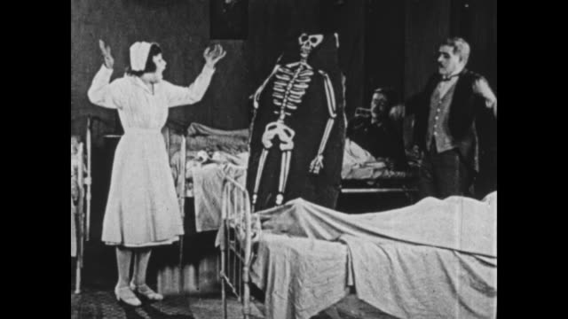 stockvideo's en b-roll-footage met 1925 nurse runs screaming from man dressed in skeleton poster - verpleegkundige