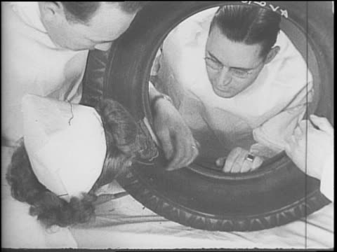 nurse selects tools for doctor / auto tire specialists perform plastic miracles as rationing hits retread industry / a man smokes outside the... - 1942 stock videos & royalty-free footage
