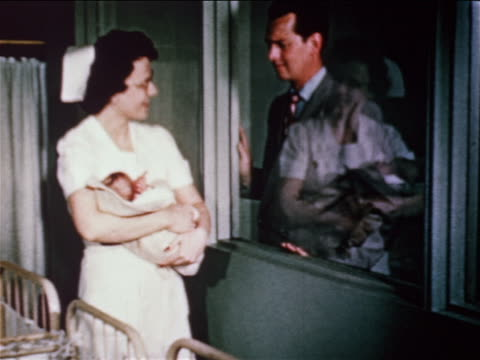 1950 nurse showing baby to man thru window in maternity ward of hospital / educational