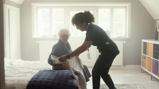 nurse showing casual clothing to senior woman - bathrobe stock videos & royalty-free footage