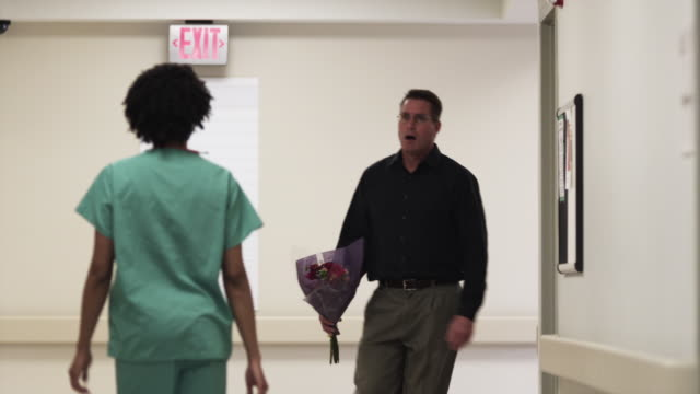 ms nurse showing direction to man with flowers in hospital corridor / payson, utah, usa - bouquet video stock e b–roll