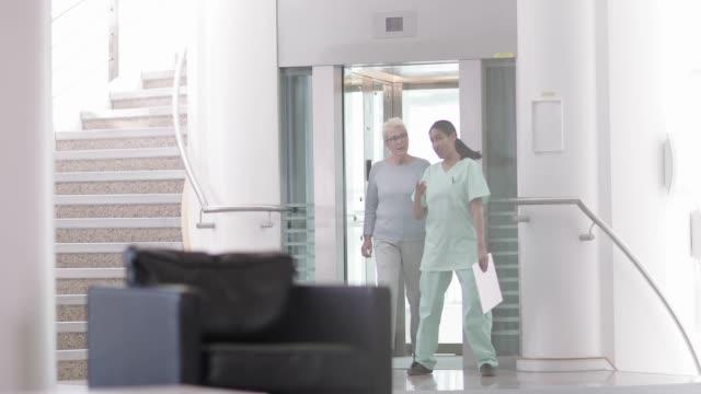 vidéos et rushes de nurse showing patient to waiting room - salle attente