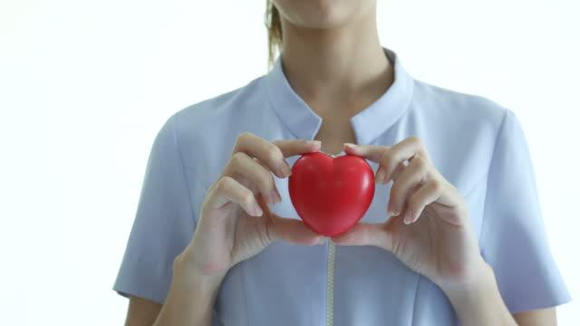 vídeos y material grabado en eventos de stock de enfermera muestra bola de corazón rojo - giving