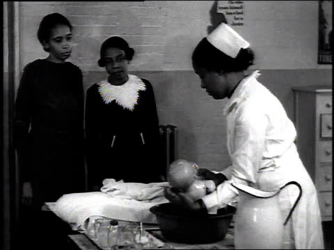 1937 montage a nurse showing two women how to bathe an infant using a dummy / new york city, new york - 1937 stock-videos und b-roll-filmmaterial