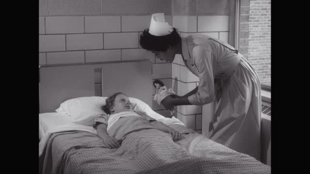 MS Nurse shows doll to young girl in bed, in hospital / United States
