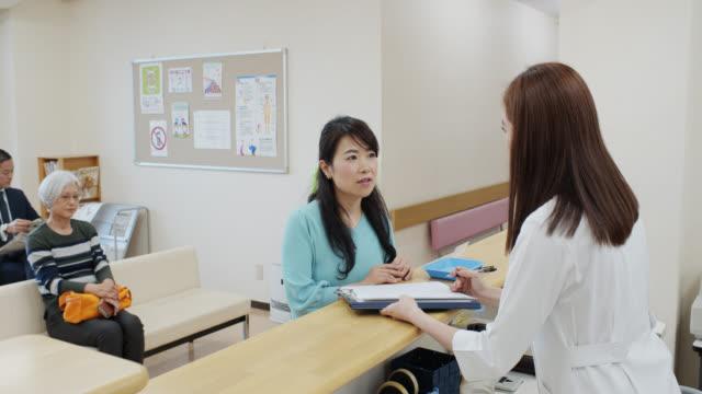 vídeos y material grabado en eventos de stock de enfermera hablando con paciente mujer en sala de espera - recepcionista