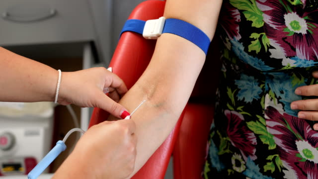 nurse stabbing medical needles to donor arm.good deed.benefits of donating blood for your body.the hand of recipient receiving the blood transfusion.close up of blood donor giving blood in medical clinic - blood bag stock videos and b-roll footage