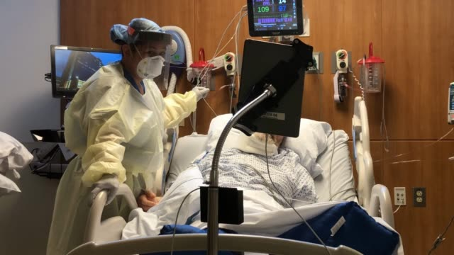 nurse stands with a covid-19 patient during a zoom video call in a stamford hospital intensive care unit , during the coronvirus pandemic on april... - pandemic illness stock videos & royalty-free footage