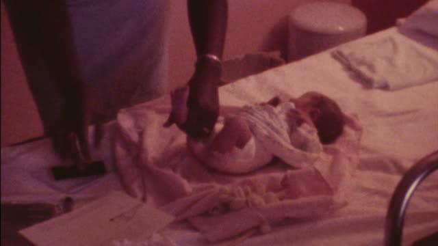 stockvideo's en b-roll-footage met nurse takes newborn's footprints. - clip kantoorartikel