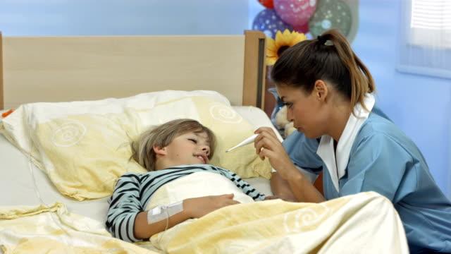 vídeos de stock, filmes e b-roll de hd dolly: enfermeira levando a temperatura da criança - enfermeira pediátrica