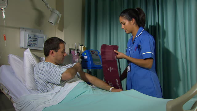 nurse taking a patient's blood pressure - examination gown stock videos & royalty-free footage