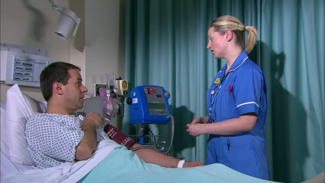 nurse taking a patient's blood pressure - untersuchungskittel stock-videos und b-roll-filmmaterial