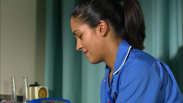 nurse taking a patient's blood pressure - examination gown stock videos and b-roll footage