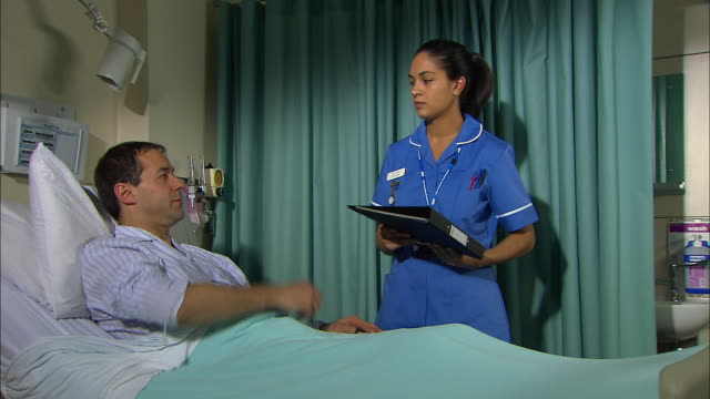 nurse taking a patient's pulse - untersuchungskittel stock-videos und b-roll-filmmaterial