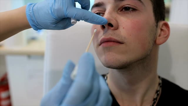 Nurse taking a sample from the human nose,close up