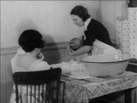 B/W 1934 nurse taking baby from bath as other woman with baby watches / WPA project / newsreel